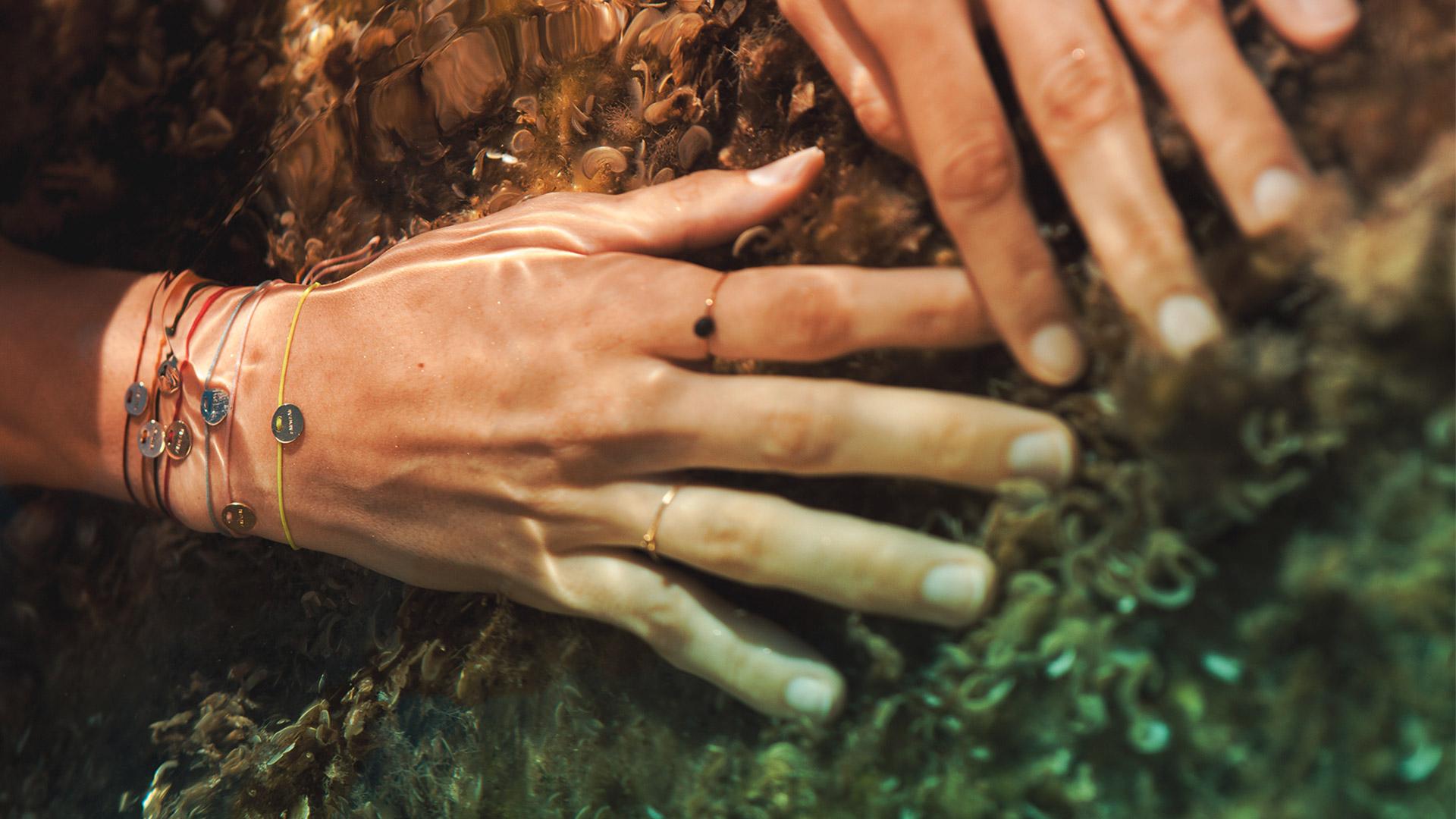 Pulseras Marma de Oro 18k y seda sumergidas en el agua